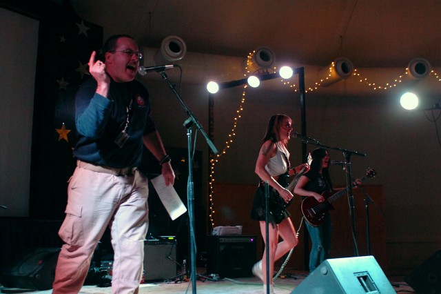 Kurk Flynn, a Q-West firefighter from Vermont sings for ThundHerStruck, a Los Angeles-based all-female ACDC tribute band, at the band's first karaoke-style concert here Jan. 26. (U.S. Army photo by Sgt. Matthew C. Cooley, 15th Sustainment Brigade public affairs)