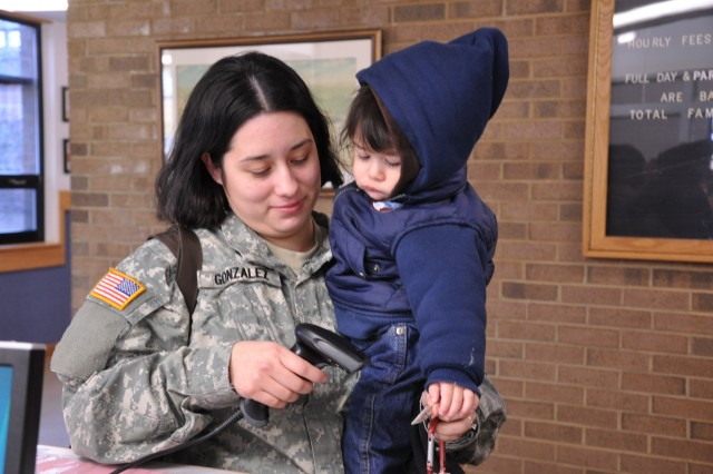 Spc. Jessica Gonzalez checks her 14-month-old son, Kristian, into the Scales Child Development Center. Scales is one of several on-post child care facilities that offer extended service hours.