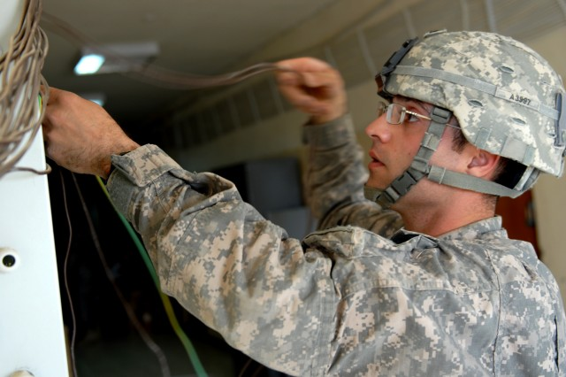 Spc. Khalid Ammari, a carpentry and masonry specialist from Florissant, Mo., assigned to Bravo Company, 46th Engineer Battalion, 225th Engineer Brigade, separates wires before connecting them to the breaker box at Joint Security Station Nasir Wa Salam, Iraq, April 25.