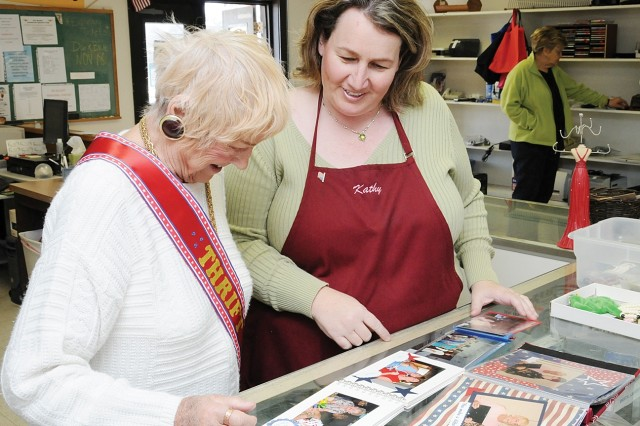 Kathy Awe, Fort Rucker Thrift Shop manager, browses old photo albums with volunteer Germaine Auxier Feb. 3 during Auxier's last day at the facility. She volunteered at the Thrift Shop for the past 43 years.