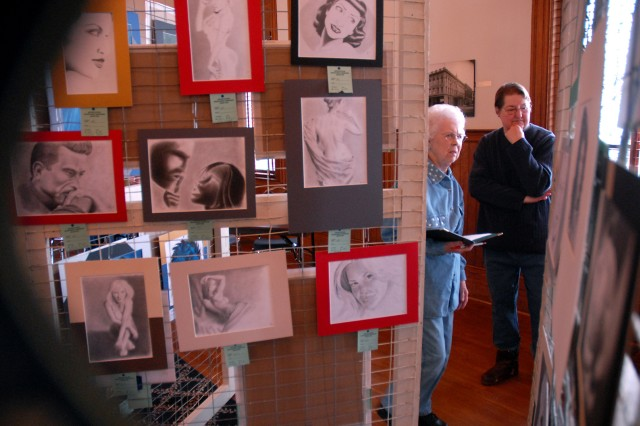 Judges Betty Clay and Pat Fuqua, of the Leavenworth County Artists' Association, study the artwork of U.S. Disciplinary Barracks inmates submitted for the Hidden Art Locked Away art show and sale, benefiting the River City Community Players, Feb. 5 at the Riverfront Community Center in Leavenworth, Kan.