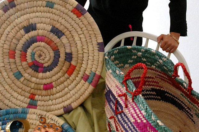Maj. Thao Reed, of Operations Group F, Battle Command Training Program, Fort Leavenworth, Kan., displays some of the baskets and home decor items made by Iraqi women that are offered through the Janan Collection Feb. 9 at her home in Leavenworth.