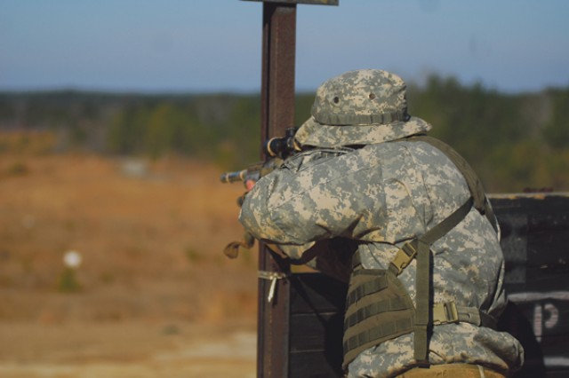 A sniper student takes position behind a half wall to aim an M24 sniper rifle at targets downrange.""