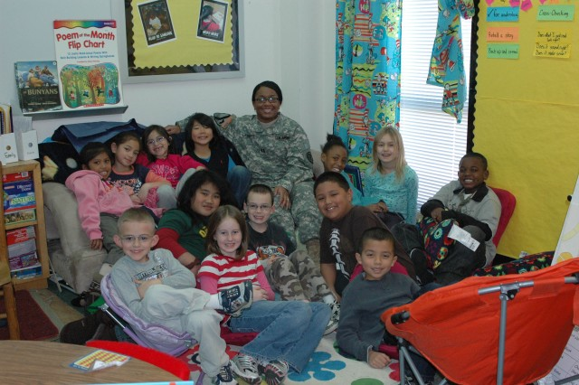 Capt. Deveilla Lambert, commander, 15th Special Troops Battalion rear detachment, 15th Sustainment Brigade, 13th Sustainment Command (Expeditionary) poses with Alice Pomeroy's second grade class at the battalion's adopted school Clarke Elementary School Jan. 7 on Fort Hood, Texas.  Lambert visits with the students and reads a book that pertains to that week's lesson every other Thursday for story time. (U.S. Army photo by Corporal Jessica Hampton, 15th Sustainment Brigade Public Affairs)