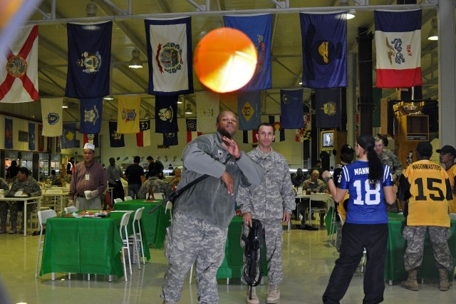 Spc. Jahari Reed, a petroleum supply specialist in Headquarters and Headquarters Company, 15th Special Troops Battalion, 15th Sustainment Brigade, 13th Sustainment Command (Expeditionary), throws a foam football towards a target hole in a game at a pre-Super Bowl party in the dining facility here, Feb. 2. (U.S. Army photo by Sgt. Matthew C. Cooley, 15th Sustainment Brigade public affairs)