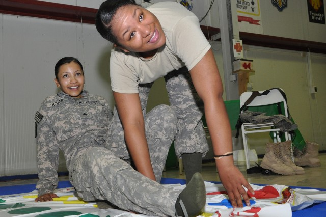 """Cpl. Rebecca Rojas [left] from Bakersfield, Calif., and Spc. Teasia Jackson from Virginia Beach, Va., both supply specialists with 204th Military Police Company, play an hour-long game of twister during a pre-Super Bowl party in the dining facility here, Feb. 2. """"We're very competitive against each other. It's more like a sibling rivalry,"""" Jackson explained. (U.S. Army photo by Sgt. Matthew C. Cooley, 15th Sustainment Brigade public affairs)"""