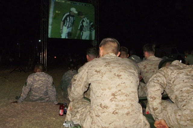 Soldiers, Airmen, Marines and Sailors sit in the grass and on folding chairs to watch Super Bowl XVIV on a 9' x 12' screen next to Haiti's international airport.  Joint Task Force - Haiti hired contractors who brought satellite dishes and outdoor screens to 11 different locations where servicemembers are living and working all around Haiti.  (U.S. Army photo by Sgt. 1st Class Dave McClain)