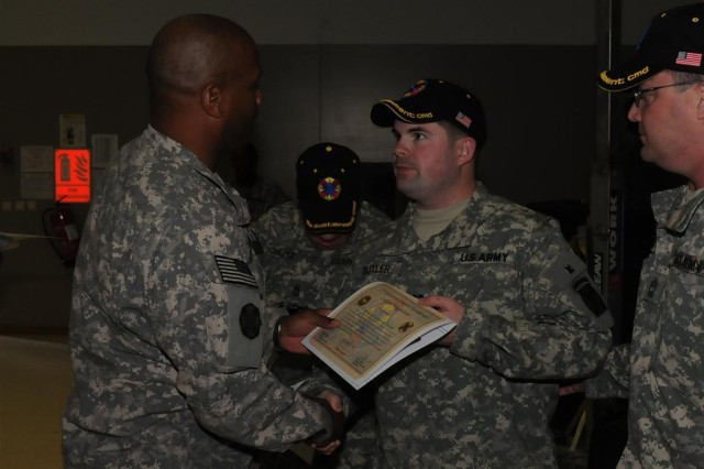 Col. Frederick Brown, assistant chief of staff of operations with the 13th Sustainment Command (Expeditionary) out of Fort Hood, Texas, and a Naches, Miss., native, hands a certificate of appreciation to Capt. Ferris W. Butler, former platoon leader with D Company, 214th Infantry Regiment, 10th Mountain, 2nd Brigade Combat Team out of Fort Drum, N.Y., at Morale, Welfare and Recreation east Feb. 5 at Joint Base Balad, Iraq. Butler, a Port Tobacco, Mass., native, participated in Operation Proper Exit, which brings Veterans who were injured in Iraq back to the country to revisit the area and share their stories.