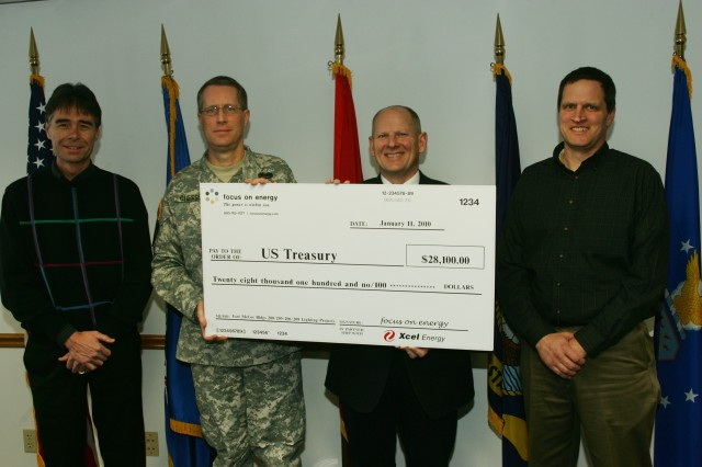 Don Keck (second from right) of Focus on Energy presents a ceremonial incentive award check to Fort McCoy Garrison Commander Col. David E. Chesser, representing Fort McCoy, for savings in an energy-conservation project. Rob Sturgis (far left) and Mike Herro (far right) represented Xcel Energy, which is Fort McCoy's energy provider.