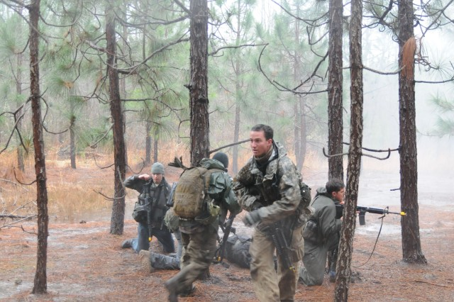 """Participants at the Robin Sage exercise help provide security during a training scenario Friday. Students preparing to become Green Berets and civilians acting as """"resistance fighters"""" were tasked with rescuing a downed pilot stuck in a tree during the event."""