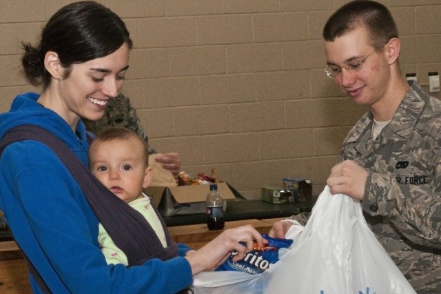 Meghan McCoy, Family readiness group leader for 407th Brigade Support Battalion, 2nd Brigade Combat Team, and her 7-month-old daughter, Stella, help package up snacks and drinks for Super Bowl themed care packages being sent to deployed Soldiers in Haiti at Green Ramp, Pope Air Force Base, Feb 3.