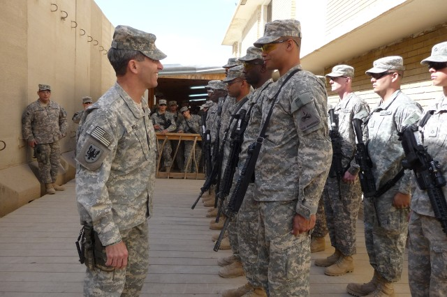 Brig. Gen. William Wolf, U.S. Army Combat Readiness/Safety Center commander, left, presents a coin to a Soldier from the 121st Brigade Support Battalion, 4th Brigade Combat Team, 1st Armored Division during a Feb. 5 visit to Iraq.