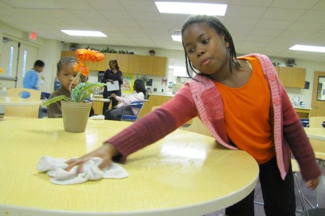 Alexis Harris, 9, is always happy to have clean-up duties following snack time at the Myra M. Garriott School Age Services Center. Elementary-age children who attend the SAS program after their school day are provided a snack and then enjoy an afternoon filled with activities, including music and drama, art and physical education.