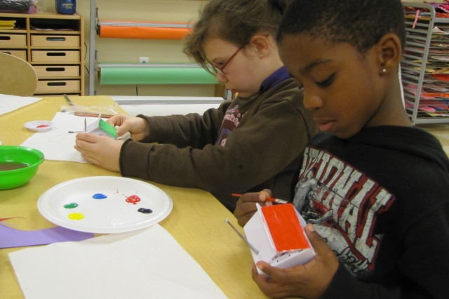 Fifth-grader Kyli Courtland and second-grader Jarea Parker work on painting milk-box radios with bright colors. The two like to spend their fun time in Arts and Crafts at the School Age Services facility.