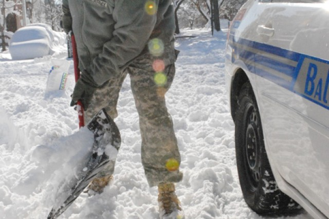 Sgt. Troy Mitchell, of Joint Force Headquarters, Maryland Army National Guard, works to free a Baltimore city police vehicle from where it was stuck in the snow Sunday, Feb. 7.