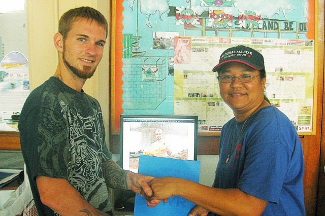 WAHIAWA, Hawaii - Outdoor Recreation Center specialist Sharon Nakai, at right, congratulates James Fowler on his second-place finish following the Freshwater Fishing Tournament, held Jan. 30, at Lake Wilson, here. Competing against six other anglers, Fowler hauled in the day's second biggest catch, a 17-inch tucunare, using a six-pound test line.