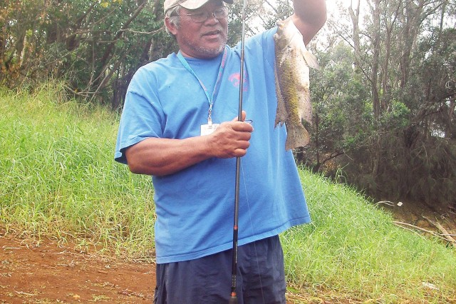 WAHIAWA, Hawaii - Pete Bautista, a recreation specialist with the Outdoor Recreation Center, admires a tilapia he hooked during a tag-and-release freshwater fishing tournament, Jan. 30, at Lake Wilson, here. Seven anglers, led by eventual winner Staff Sgt. Tristan Peltier, 732nd Military Intelligence Battalion, took part in the first-ever competition.