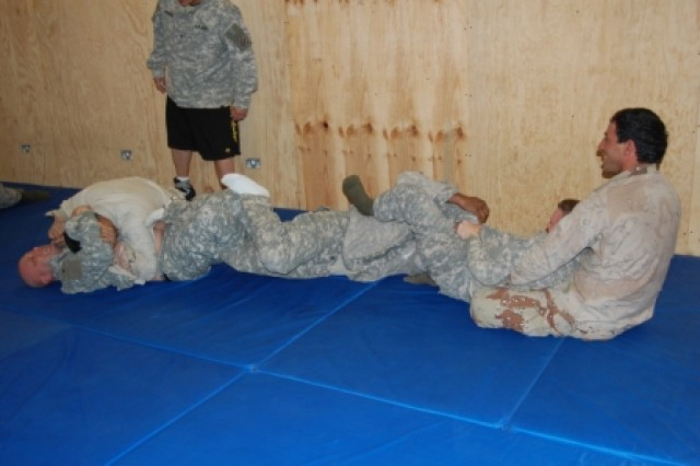 Soldiers from the 1st Battalion, 15th Infantry Regiment, 3rd Heavy Brigade Combat Team, 3rd Infantry Division, and the 4th Battalion, 8th Iraqi Army Division, grapple during a competition Feb. 7, 2010, as part of the level-two combatives course at Forward Operating Base Echo, Iraq.