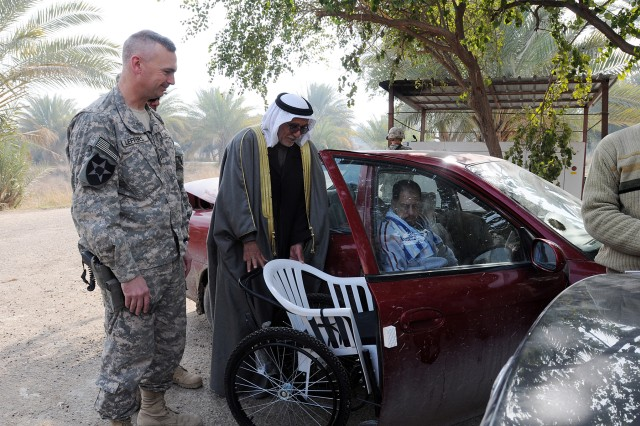 BAGHDAD - Lt. Col. John Leffers, a native of Utica, N.Y., and the commander of 1st Battalion, 38th Infantry Regiment, 4th Stryker Brigade Combat Team, 2nd Infantry Division, offers a uniquely designed wheelchair to a former member of the Sons of Iraq in the Aqur Quf area Feb. 10. The chair was designed to enable recipients to buy inexpensive replacement parts at a local market. (U.S. Army photo by Sgt. Samantha Beuterbaugh, 366th MPAD, USD-C)