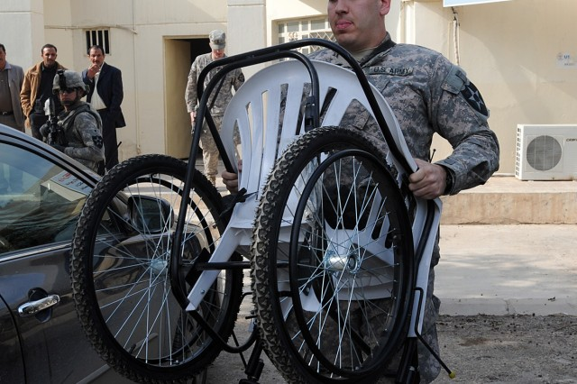 BAGHDAD - 2nd Lt. Jacob Boesen, a native of Mclean, Va., with Headquarters and Headquarters Company, 1st Battalion, 38th Infantry Regiment, 4th Stryker Brigade Combat Team, 2nd Infantry Division, carries a wheelchair to the vehicle of its recipient, a former member of the Sons of Iraq. Two wheelchairs, designed to enable the recipients to buy inexpensive replacement parts on the market, were delivered Feb. 10 in the Aqur Quf area. (U.S. Army photo by Sgt. Samantha Beuterbaugh, 366th MPAD, USD-C)