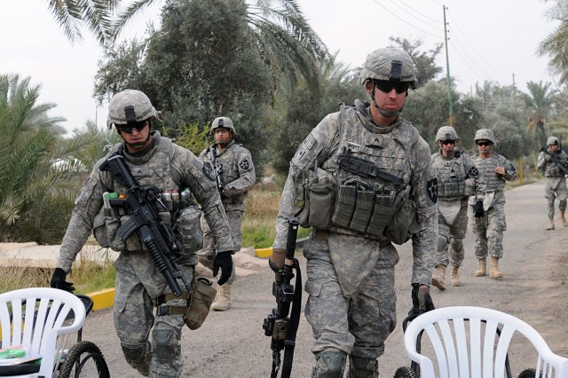 BAGHDAD - Sgts. Joe Gray (left) from Lake Dallas, Texas, and Andrew Whitesand, from Pueblo, Colo., roll two handcrafted wheelchairs up a road Feb. 10. The infantry team leaders with Headquarters and Headquarters Company, 1st Battalion, 38th Infantry Regiment, 4th Stryker Brigade Combat Team, 2nd Infantry Division, delivered the chairs before the weekly shaykh council meeting in the Aqur Quf area. (U.S. Army photo by Sgt. Samantha Beuterbaugh, 366th MPAD, USD-C)