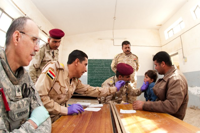 AL UWESAT, Iraq - Capt. Ahmed Zyara, a physician with 1st Iraqi Division, examines an Iraqi boy whose father brought him to a one-day medical clinic operated by Iraqi and U.S. military medical staff in the east-Anbar village of Al Uwesat, Iraq, Feb. 11. At right is Sgt. Leo Touzjian, a medic with 3rd Battalion, 157th Field Artillery Regiment, which is attached to 1st Brigade, 82nd Airborne Division (Advise and Assist). (U.S. Army photo by Spc. Michael J. MacLeod, 1/82 AAB, USD-C)
