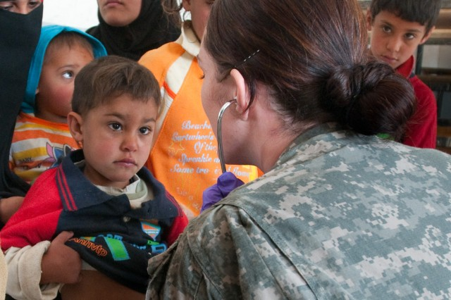 AL UWESAT, Iraq - Sgt. Bethany Smith, a medic with 1st Brigade, 82nd Airborne Division (Advise and Assist), examines a young boy with cold symptoms in a one-day medical clinic operated by Iraqi and U.S. military medical staff in the village of Al Uwesat, Iraq, Feb. 11. The mother of the boy explained to Smith that they must travel two hours to see a doctor. (U.S. Army photo by Spc. Michael J. MacLeod, 1/82 AAB, USD-C)
