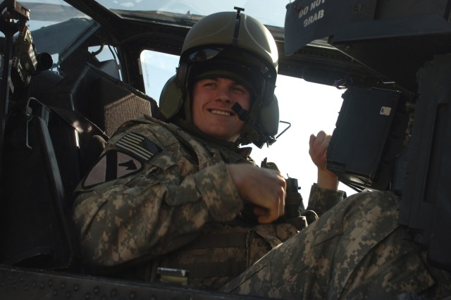 CAMP TAJI, Iraq - Spc. Beau Messer, from Royal Oak, Mich., a crew chief in Company B, 615th Aviation Support Battalion,1st Air Cavalry Brigade, 1st Cavalry Division, U.S. Division-Center, sits in the front seat of an AH-64D Apache attack helicopter shortly before flying in the aircraft for the first time Jan. 25. Messer was selected for the incentive as part of a program that allows Apache crew chiefs to fly in the aircraft for outstanding performance in their careers.