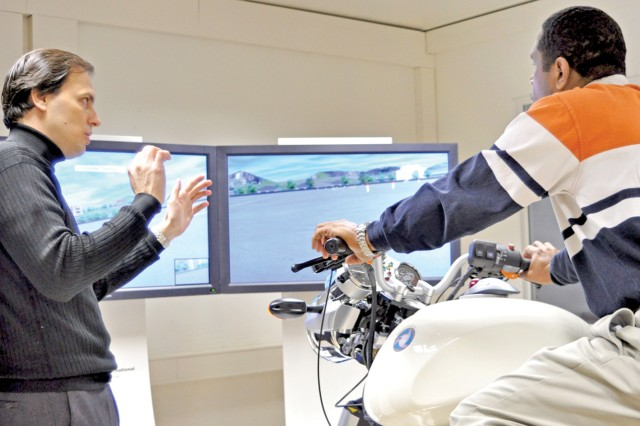 Todd Roberts explains the functions of the new motorcycle simulator on Wackernheim's McCully Barracks to robert Myrick.