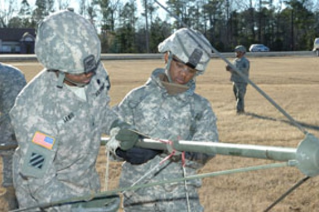 Two Soldiers on the M31E1 Biological Integrated Detection System crew set up a site on Pine Bluff Arsenal.