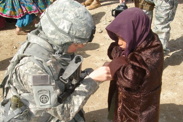 Spc. Logan Purtlebaugh, a chaplain assistant with the 782nd Brigade Support Battalion, 4th Brigade Combat Team, 82nd Airborne Division, talks to a young Afghan girl while participating in an operation to deliver tents and blankets to victims of flooding in the Kandahar province, Afghanistan.  Led by the 205th Corps Afghan National Army, 43 tents and over 200 blankets were distributed to the citizens of Haji Aziz Kalay.