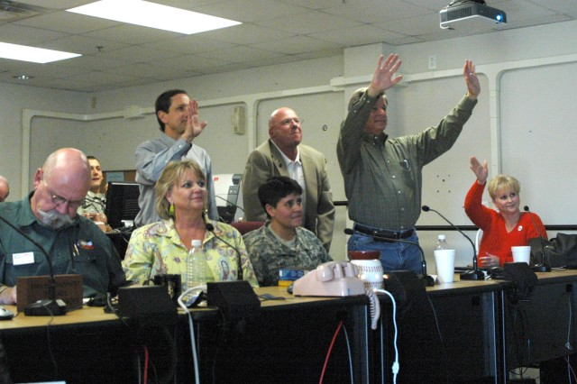 Lisa Phelps, wife of Col.  Larry Phelps, commander of the 15th Sust. Bde., 13th ESC and  members of the Belton community wave good bye to Col. Larry Phelps, commander of the 15th Sust. Bde., 13th ESC, and his command team during a video teleconference at the brigade's headquarters building, here Jan. 22.  (U.S. Army photo by Cpl. Jessica Hampton, 15th Sustainment Brigade Public Affairs)