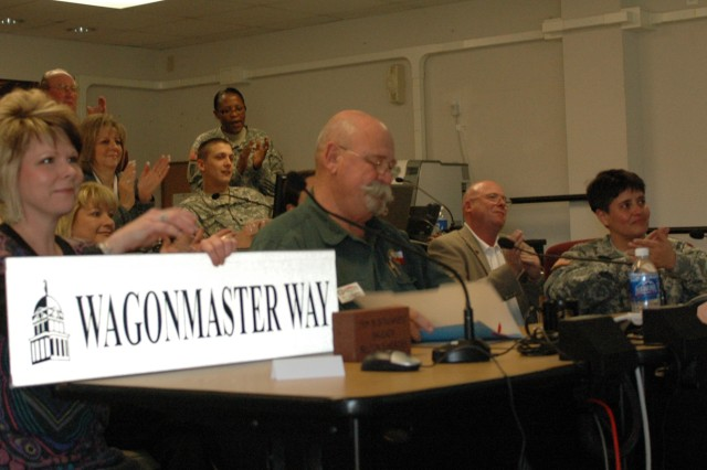 "FORT HOOD, Texas- Stephanie O'Banion, president of the Belton area Chamber of Commerce holds a street sign as Jim Covington, the mayor of Belton, Texas reads a proclamation to Col. Larry Phelps, commander of the 15th Sust. Bde., 13th ESC, and his command team during a video teleconference at the brigade's headquarters building, here Jan. 22.   The street sign that reads, ""Wagonmaster Way"" will be hung to designate an area in Belton's Yettie Polk Park.  Covington stated that a covered wagon with hopes of a story board to share the brigade's story with the park's visitors will be place there as well. (U.S. Army photo by Cpl. Jessica Hampton, 15th Sustainment Brigade Public Affairs)"
