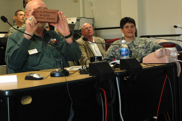 "FORT HOOD, Texas- Jim Covington, Mayor of Belton, Texas shows an engraved brick to Col. Larry Phelps, commander of the 15th Sust. Bde., 13th ESC and his command team during a video teleconference at the brigade's headquarters building, here Jan. 22.  The brick that reads, ""15th Sustainment Brigade, Belton's Heroes"", will be displayed in Belton's Patriot Way Brickwalk that is located in historic downtown Belton.  Covington also read in the proclamation that a tree will be planted with a monument in Belton's Heritage Park in the spring to pay tribute to their heroes of the 15th Sustainment Brigade. (U.S. Army photo by Cpl. Jessica Hampton, 15th Sustainment Brigade Public Affairs)"