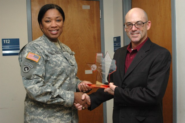 """Perry Jefferies, a blood donor recruiter for the Robertson Blood Center on Fort Hood presented an """"Award of Recognition"""" for the highest number of volume blood donors from a brigade sized element within the 13th Sustainment Command (Expeditionary) in 2009 to Sgt. Maj. Kendra Wallace, the 15th Sust. Bde.'s rear detachment senior noncommissioned officer, who accepted the award on behalf of the """"Wagonmasters"""". (U.S. Army photo by Cpl. Jessica Hampton, 15th Sustainment Brigade Public Affairs)"""