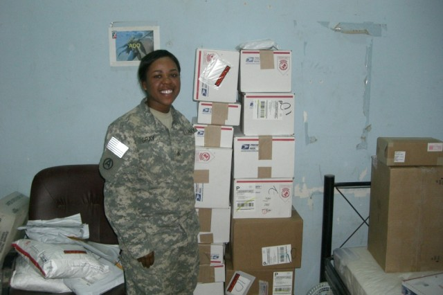 Sgt. Kimberly Gray, from Lexington, Ky., poses with a delivery in the mail room for Headquarters and Headquarters Company, 264th Combat Sustainment Support Battalion, 15th Sustainment Brigade, 13th Sustainment Command (Expeditionary). (Courtesy photo)