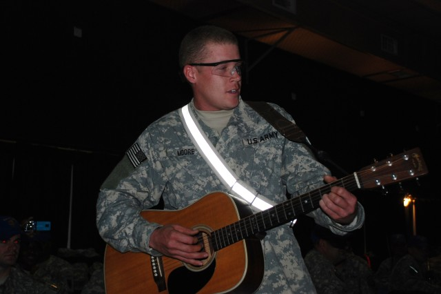 Cpl. Joshua Moore of Gilbert, Ariz., a track vehicle mechanic assigned to the 3666 Support Maintenance Company, 541st Combat Sustainment Support Battalion, 15th Sustainment Brigade, 13th Sustainment Command (Expeditionary), sings and plays his guitar for entertainment during the dining-in on Dec. 28.