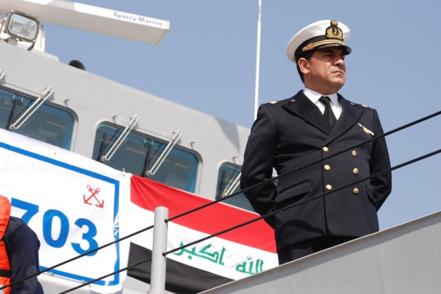 An Iraqi Naval officer reviews the parade of ships at the Umm Qasr port in southern Iraq, Feb. 14, during the christening of the Majed 703 and Shomokh 704. Eighty-five percent of all Iraqi oil exports go through the ports that the new ships are assigned to protect.