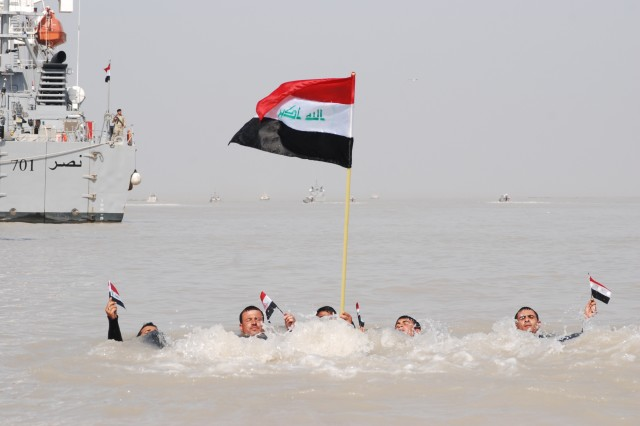 """Swimmers from the Iraqi Navy, nicknamed """"frogmen,"""" swim through the waters of the Umm Qasr port in southern Iraq, Feb. 14. The display was part of the christening of the Majed 703 and Shomokh 704, the newest ships in the Iraqi Navy."""