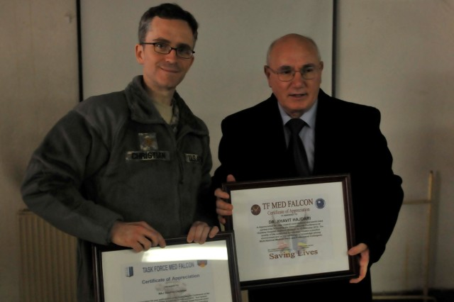 Maj. Stephen Christian, Florence, S.C., chief radiologist at the Camp Bondsteel Hospital for Multi-National Battle Group-E; and Dr. Xhavit Hajdari, director of the Gjilan/Gnjilane Hospital; show off their certificates of appreciation that they exchanged following at the medical Regional Grand Rounds event held Feb. 15 in Gjilan/Gnjilane.
