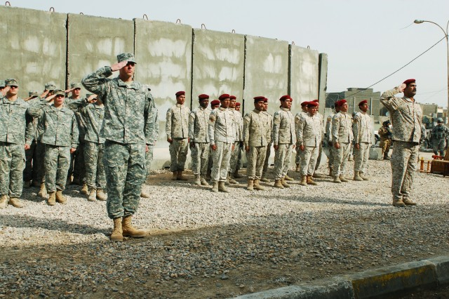 Soldiers from 1st Battalion, 77th Armor Regiment, 4th Brigade, 1st Armored Division, stand next to soldiers from the 53rd Brigade, 14th Iraqi Army Division, during the Al Hindiyah camp return ceremony in Basrah, Iraq, Jan 29.