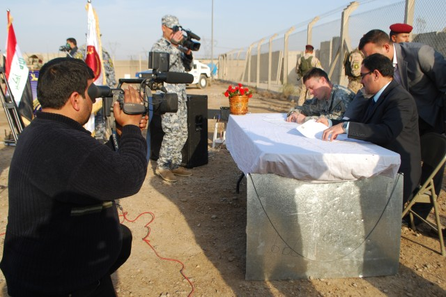 BAGHDAD - Capt. Tad Grani, from Providence, RI, and Al Hadad, a representative of the Iraqi prime minister, sign the documents necessary Feb. 15 to hand over Joint Security Station 799 to the Iraqi Government. (Army photo by Spc. Rebecca Schwab, 2nd BCT PAO, 10th Mtn. Div. USD-C)