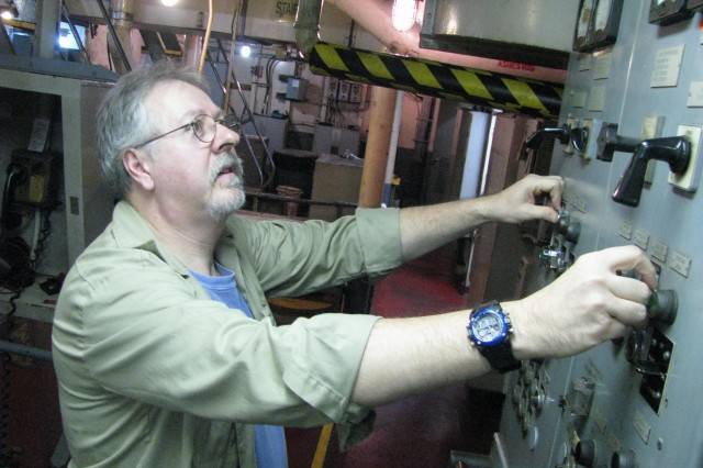 First Engineer Jim Gallant adjusts controls in the engine room of the dredge <i>McFarland</i> during recent operations at the mouth of the Mississippi River.