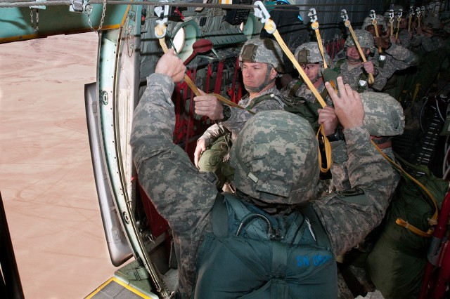 Col. Mark R. Stammer, commander of 1st Brigade, 82nd Airborne Division (Advise and Assist), hands off his universal static line as he moves to parachute from a C-130 aircraft at Al Asad Airbase, Iraq, Feb. 12. Refreshing the airborne proficiency of his paratroopers is the first step toward the goal of combined U.S. – Iraqi airborne training exercises following Iraqi national elections in early March.
