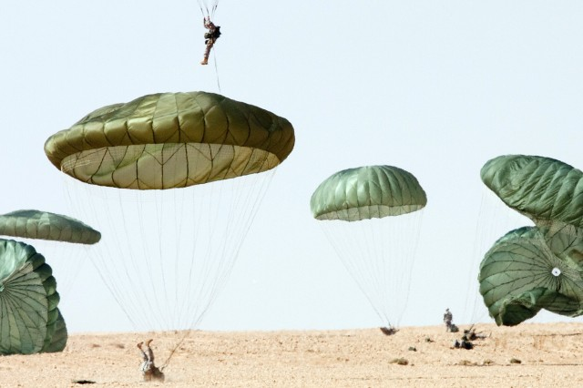 "Paratroopers with 1st Brigade, 82nd Airborne Division (Advise and Assist), land on a drop zone near Al Asad Airbase, Iraq, Feb. 12, as part of a training exercise they hope will lead to combined U.S. – Iraqi training jumps. The jumper rolling on his back is performing a ""parachute landing fall,"" a maneuver that dissipates the energy of impact, avoiding injury to the paratrooper."