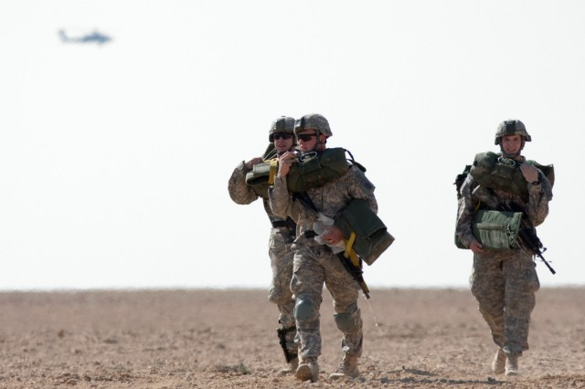 Three paratroopers with 1st Brigade, 82nd Airborne Division (Advise and Assist), move off a drop zone near Al Asad Airbase, Iraq, Feb. 12, as part of a training exercise they hope will lead to combined U.S. – Iraqi training jumps and an enduring strategic partnership. For security, an Apache helicopter flew along the drop zone perimeter throughout the training exercise.