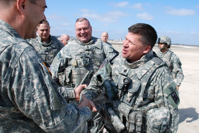 Maj. Gen. Simeon Trombitas, U.S. Army South commander, and Lt. Col. Dennis Lewis, 201st Military Intelligence Battalion commander, shake hands before the latter boards a charter aircraft on Lackland Air Force Base's Kelly Field Annex Feb. 14. Battalion Command Sgt. Maj. Michael Ables stands to the right of his commander. Lewis, Ables and approximately 130 other Soldiers of the battalion are deploying to Afghanistan for a year. (U.S. Army photo by Gregory Ripps, 470th Military Intelligence Brigade/RELEASED)