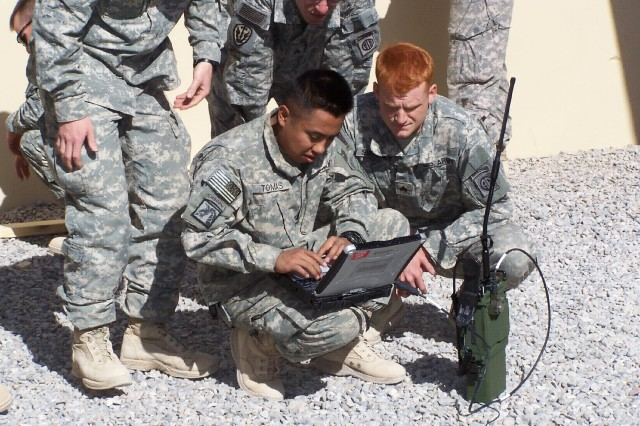 FOB WALTON, KANDAHAR PROVINCE, Afghanistan - SGT Isidro Thomas, CPT Ryan Kenny, and SGT Ian Sweeney connect to OEF SIPRNet via PRC-117G during RTO/Operator Training for the first time.