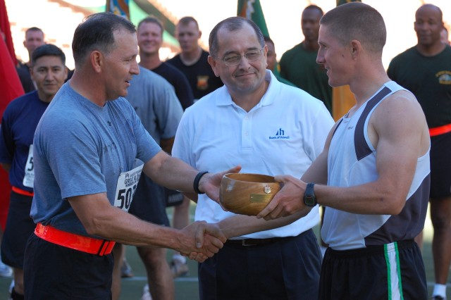 Lt. Gen. Benjamin R. Mixon, commanding general, U.S. Army Pacific (left), presents the Sounds of Freedom award for the third place male runner to Conor Lucas-Rober, a Marine from Kaneohe, for his time of 46:42, as Vince Barfield, Bank of Hawaii representative, looks on during the awards ceremony of the 2010 Great Aloha Run in the Aloha Stadium, Honolulu Feb. 15. The Bank of Hawaii sponsored the Sounds of Freedom awards, which were given to military participants in the categories of male and female first, second and third place finishers; largest formation; and largest branch of service. (U.S. Army photo by Staff Sgt. Tim Meyer, 25th Infantry Division Public Affairs.)