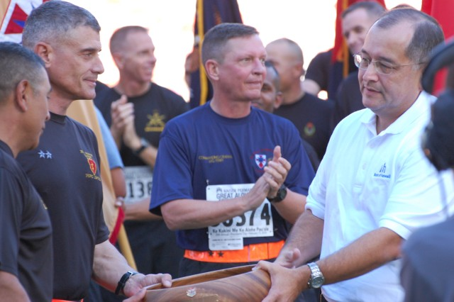 Vince Barfield, Bank of Hawaii representative (right) presents the award for the largest unit running in formation to Maj. Gen. Robert L. Caslen, Jr., commander, 25th Infantry Division and Division Command Sgt. Major Frank M. Leota during the awards ceremony of the 2010 Great Aloha Run in the Aloha Stadium, Honolulu Feb. 15. The Bank of Hawaii sponsored the Sounds of Freedom awards, which were given to military in the categories of male and female first, second and third place finishers; largest formation; and largest branch of service. (U.S. Army photo by Staff Sgt. Tim Meyer, 25th Infantry Division Public Affairs.)